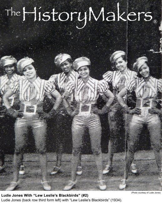 Black and white photo shows six Black women standing in two lines of three and dressed in a uniform of light-toned satiny shorts, vertical striped shirts, suspenders, ties, and satin newsboy caps. All wear light-toned tap shoes.