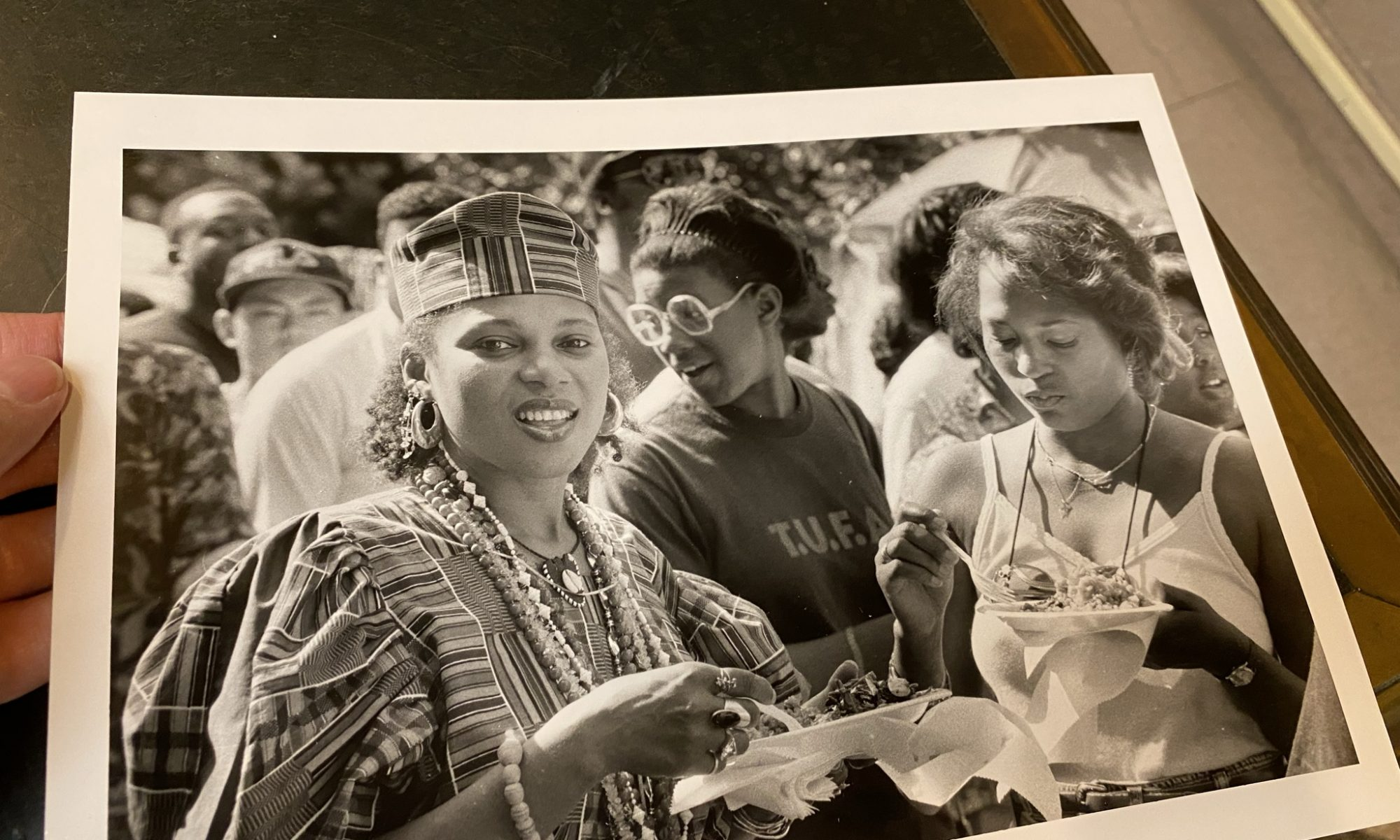Black and white photo. Tiye Olufumilayo (CQ) (L) and Monica Gaskin (R) are having yellow rice and collard greens. Photograph by Akira Suwa, June 9, year unknown. Courtesy of Free Library of Philadelphia, Print and Picture Collection.